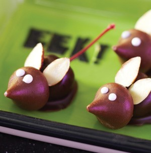 Hershey Kiss attached to chocolate-covered maraschino cherry, decorated with almonds and frosting