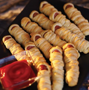 Hot dogs wrapped in pastry with a side of ketchup