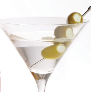 Martini in a martini glass with three green olives on a skewer