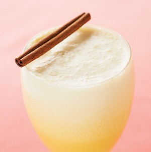 Glass of orange cream garnished with cinnamon stick