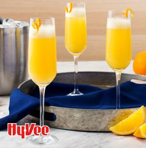 Champagne flutes filled with mimosas and garnished with orange peels