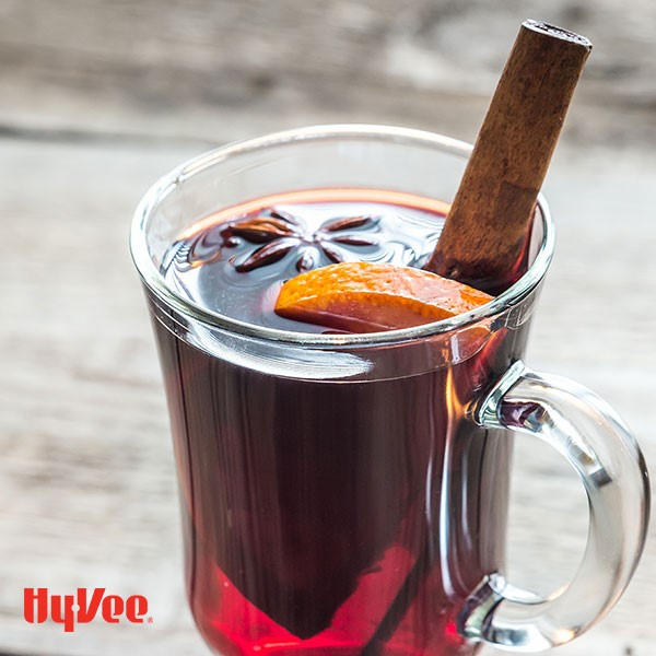 Glass clear mug filled with red mulled wine and garnished with whole star anise, cinnamon stick, and orange wedge