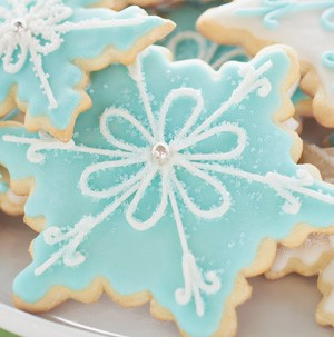 Snowflake-shaped sugar cookies topped with blue and white icing