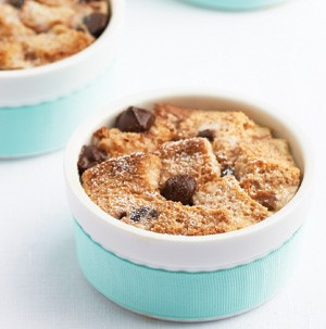 Bread pudding in a blue bowl with chocolate chips on top