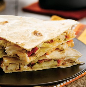 Plate of stacked quesadillas filled with Alaskan crab and artichoke