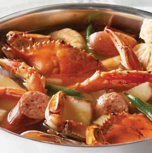 Large stockpot filled with shelled crab, sausage, and green beans