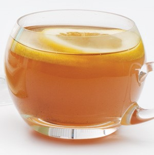 Clear mug of apricot-apple cider topped with lemon slices
