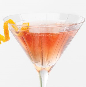 Sparkling cranberry martini garnished with a citrus peel