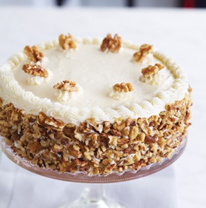 White frosted cake topped with walnuts on a cake stand