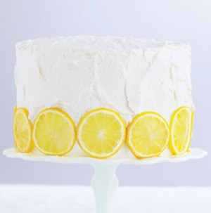Vanilla frosted cake on a cake stand garnished with lemon slices