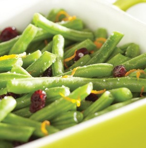 Yellow casserole dish filled with green beans, orange zest, and dried cranberries
