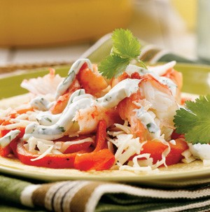 Tortilla topped with Alaska crab meat, red bell peppers, cheese, cilantro and sour cream