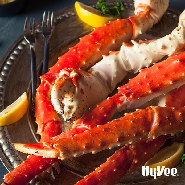 Platter of Alaska crab legs with lemon wedges and eating utensils