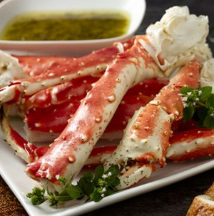 Plate of crab legs with side of dipping sauce