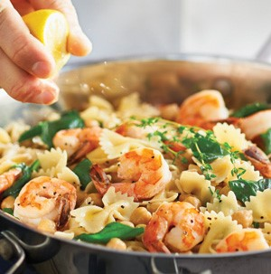 Skillet filled with tail-on shrimp, bow tie pasta, and fresh greens for garnish