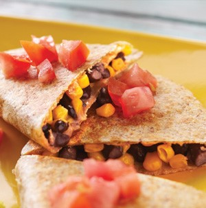 Plate of black bean and corn quesadillas topped with fresh tomato