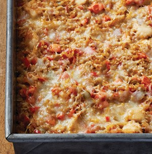 Quinoa casserole filled with chicken, carrot, onion, celery and red bell pepper and topped with Mexican blend cheese