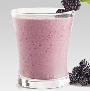 Glass filled with pink blackberry smoothie, garnished with fresh blackberries