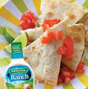Quesadillas cut into wedge topped with fresh chopped tomatoes and lime wedges with bottle of ranch