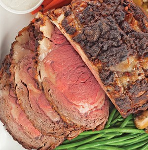 Partially sliced prime rib roast served with side of fresh green beans
