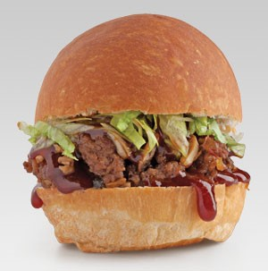 Bun topped with ground meat, sauce, lettuce, and onions