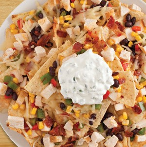 Tortilla chips topped with black beans, corn kernels, diced meat, chopped cooked bacon, and a dollop of sour cream on top