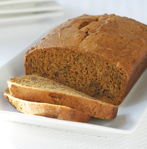 Sliced whole grain bread loaf on a white square plate
