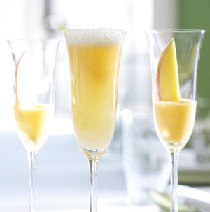 Glass flutes filled with bellini mocktails and sliced apricot