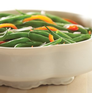 Casserole dish filled with shallots, fresh green beans, and sliced bell peppers