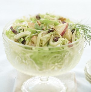 Bowl of apple-fennel slaw garnished with fennel sprigs