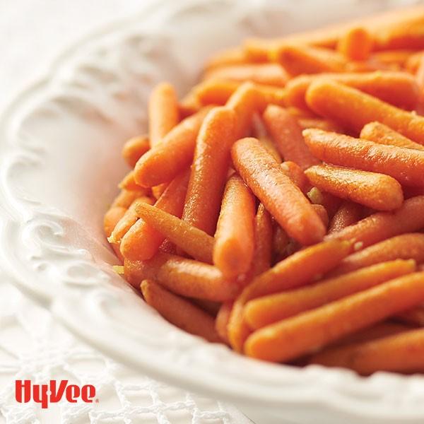 White serving platter filled with ginger glazed baby carrots