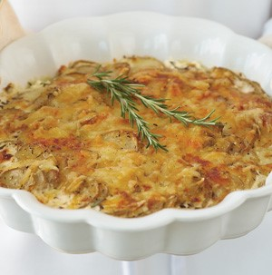 Cheesy potatoes in a scalloped white casserole dish garnished with fresh rosemary sprigs