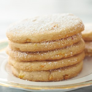 Stacked orange cookies on a gold rimmed plate and dusted with powdered sugar