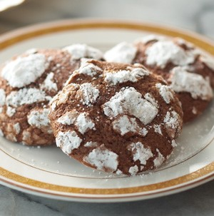 Chocolate crinkle cookies dusted with powdered sugar on a white and gold rimmed plate