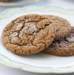 Three stacked ginger molasses crackle cookies with a dusting of powdered sugar on top
