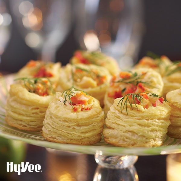 Platter of crab and brie puffs, garnished with fresh dill
