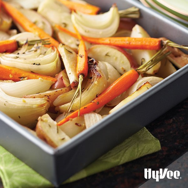 Dark grey pan filled with potato and white onion wedges and whole roasted carrots