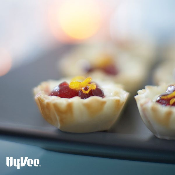 Tray of cranberry-orange brie cups, garnished with orange zest