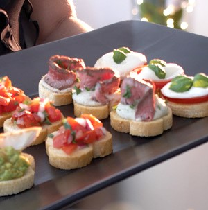 Platter of crostini with white bean spread and beef tenderloin