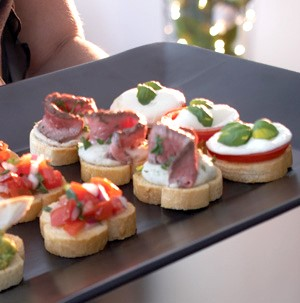 Black serving platter topped with mini crostinis