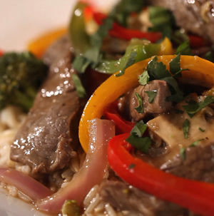 Sliced sirloin steak mixed with sliced red and yellow peppers and red onions and topped with fresh herbs