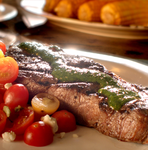 Plate of steak covered in chimichurri sauce served with cherry tomatoes