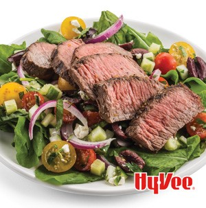 Salad topped with tomatoes, olives, red onions, and thinly cut steak