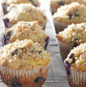 White muffin tins filled with bluberry crumb muffins on a wire rack