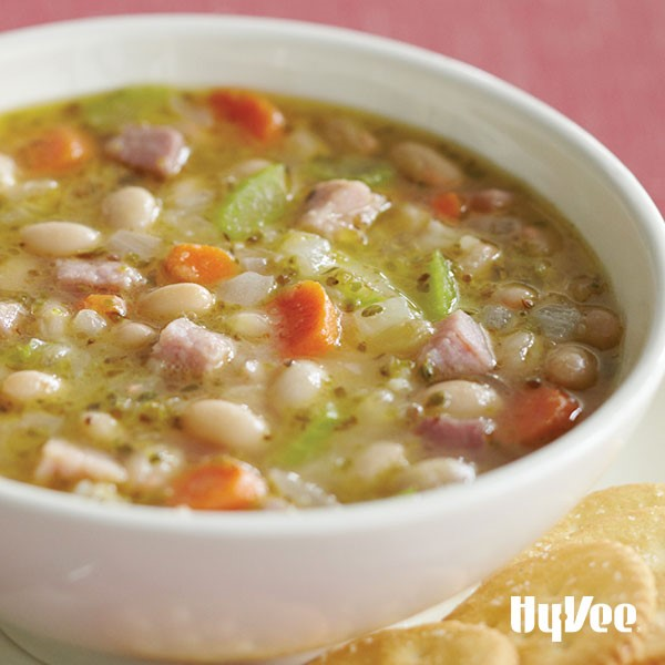 White bowl of soup filled with broth, white beans, sliced carrots, chopped celery, and cubed ham