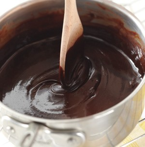 Pot of chocolate sauce with wooden spoon