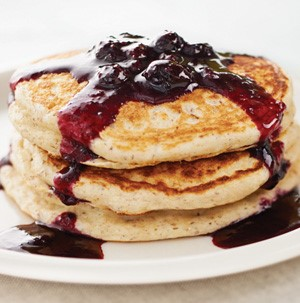 Stack of blueberry cream pancakes with blueberry sauce on a white plate