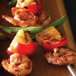 Shrimp, red bell pepper, pineapple and sugar snap peas on metal skewers