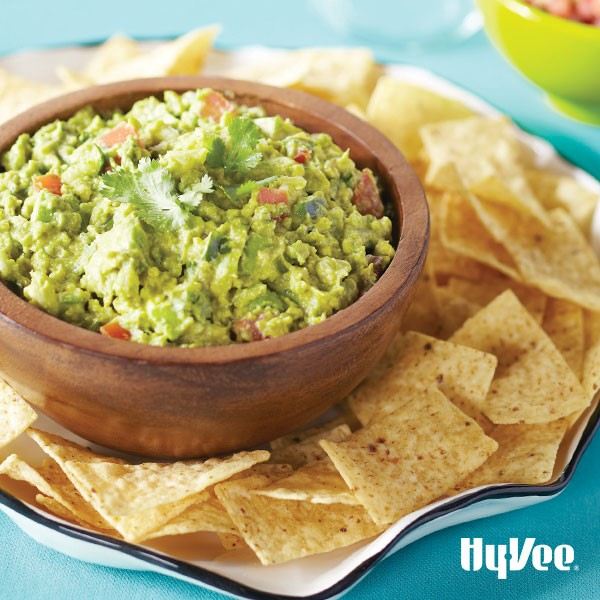 Wooden bowl of guacamole with cilantro on top set on a plate with tortilla chips