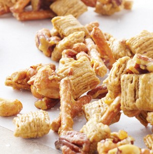 A combination of cereal, pretzel sticks, peanuts and pecans